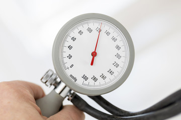Mann hält Blutdruckmeßgerät