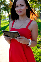 Young Woman With Tablet Computer In City Park Backlit at Sunset