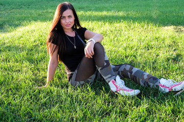Full-length beautiful woman sitting on the grass