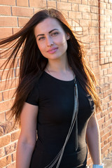 Beautiful young brunette in black shirt  posing outdoor against