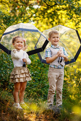 Children with umbrellas under sunny rain