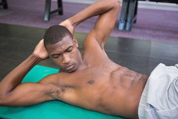 Shirtless man doing abdominal crunches in gym