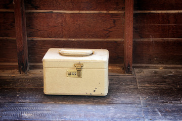 An old vintage cream train case or makeup luggage