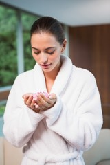 Woman in bathrobe holding flowers in spa