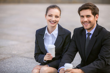 Business people drinking coffee outside.