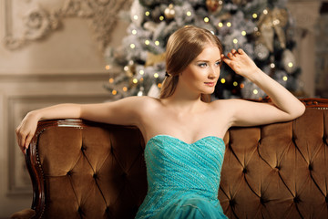 Luxury blonde in interior New Year. Young beautiful trendy girl