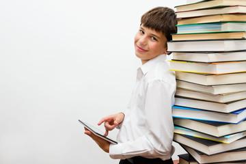 Подросток с планшетным компьютером среди книг