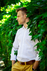 Handsome fashionable young man standing in the leaves of a wild