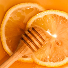 Golden honey with wooden dipper and lemon slice.- medicine from