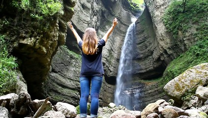 A young girl receives energy from the beautiful waterfall