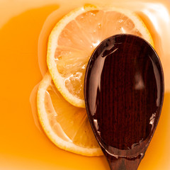 Golden honey with wooden spoon and lemon slice.- medicine from n