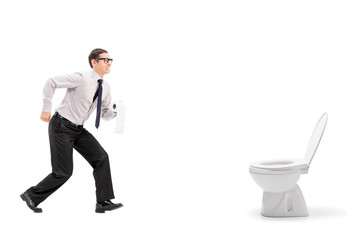 Man rushing to a urinal and holding toilet paper