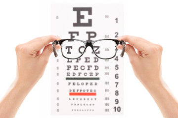 Hands holding glasses in front of an eye chart