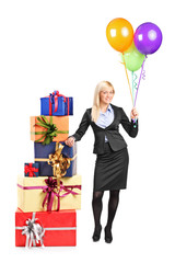 Businesswoman standing by a pile of presents