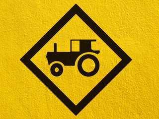 tractor crossing warning traffic sign painted on a stucco wall