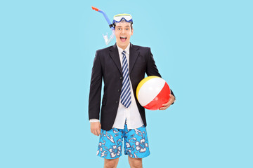 Excited businessman with snorkel and a beach ball