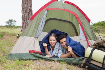 Happy couple lying in tent on countryside landscape