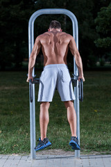 Muscular man on the outdoor gym