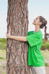 Female environmental activist hugging tree trunk