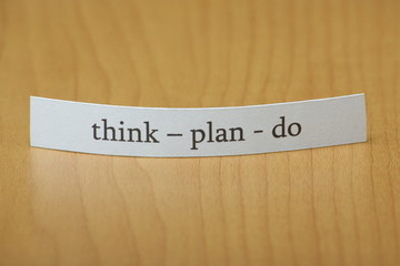 Think Plan Do on a slip of paper on a wooden desktop