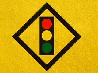 Traffic light signal sign painted on a stucco wall outside