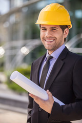 Architect in yellow hardhat holding plan.