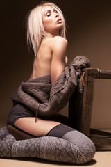 Beautiful blond wearing cardigan and stockings by the chair