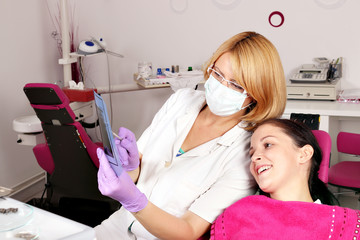 female dentist and girl patient examine x-ray