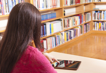 Rear view of a female student using a tablet computer in a libra