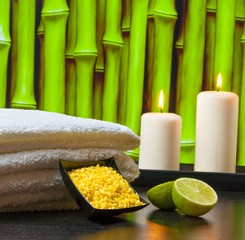 Spa massage with towel stacked sea salt candles and lime