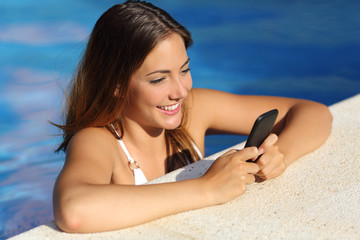 Girl using a smart phone in a pool in summer vacations