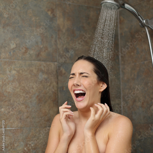 Leinwanddruck Bild Disgusted woman screaming in the shower under cold water