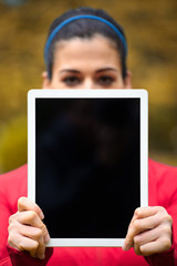 Sporty woman showing blank digital tablet screen