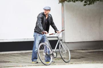 Mann mit Fahrrad vor Schaufenster