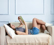 Young woman is lying on the sofa