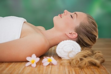 Peaceful blonde lying on bamboo mat with flowers