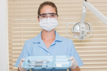Dental assistant in blue holding tray of tools