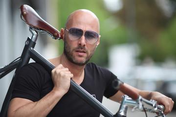Mann mit Fahrrad und Sonnenbrille