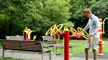 senior park (exercise machines) with benches- man strengthens