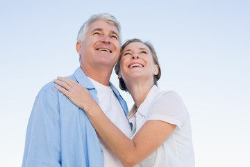 Happy casual couple embracing under blue sky