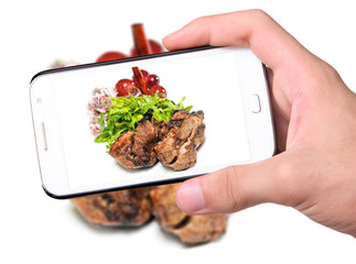 Hands taking photo grilled meat with smartphone