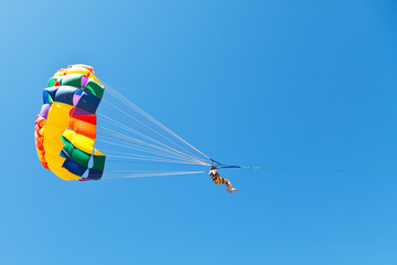 woman parasailing on parachute in blue sky