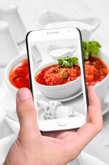 Hands taking photo red borsch with smartphone