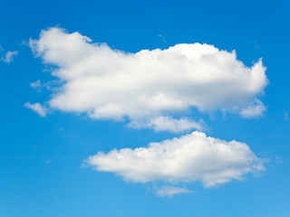 two fluffy white clouds in blue sky