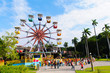 colorful ferris wheel in the playground against the blue sky - 69004412