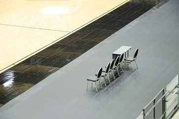 Empty chairs for coaches on the basketball arena.