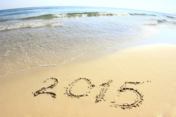 "New year background of beach with ""2015"" drawn in the sand"