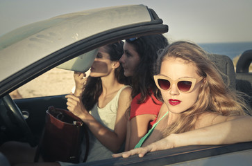 three young women on a car