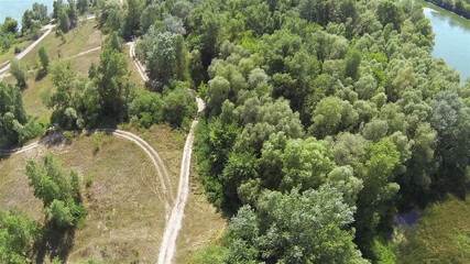River, wood and dirt road. Aerial top view