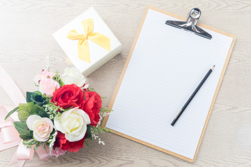 Wooden Clipboard attach planning paper with pencil beside rose b